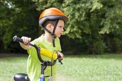 儿童骑自行车者在公园 免版税库存照片