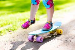 儿童骑马滑板在夏天公园 免版税库存照片