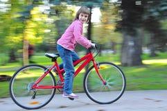 儿童骑马自行车在公园 库存图片