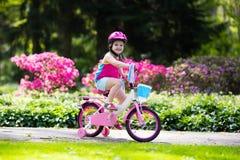 儿童骑马自行车 在自行车的孩子 免版税图库摄影