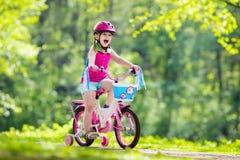 儿童骑马自行车 在自行车的孩子 免版税库存图片