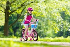 儿童骑马自行车 在自行车的孩子 库存图片