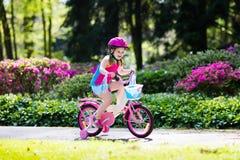 儿童骑马自行车 在自行车的孩子 免版税库存照片