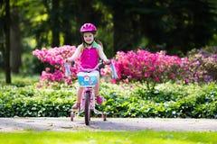 儿童骑马自行车 在自行车的孩子 图库摄影