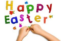 儿童从黏土和词塑造的` s手在白色背景的复活节快乐 图库摄影
