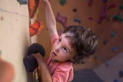 儿童登山人攀登墙壁 免版税库存图片
