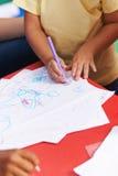 儿童绘画的手在纸的 库存图片