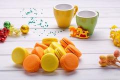 儿童` s党,新年概念 蛋白杏仁饼干和两个杯子在白色木背景 免版税库存图片