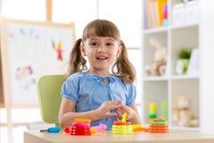儿童` s创造性 孩子从黏土雕刻 逗人喜爱的小女孩从在桌上的彩色塑泥铸造在托儿所 库存图片