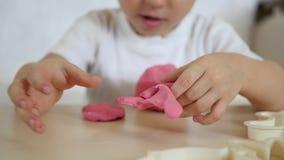 儿童` s创造性 孩子形成从桃红色面团的图在桌特写镜头 逗人喜爱的儿童` s彩色塑泥 影视素材