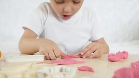 儿童` s创造性 小男孩形成从颜色测试的图在桌 逗人喜爱的儿童` s彩色塑泥 影视素材