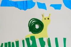 儿童` s在草的补花蜗牛 免版税库存图片