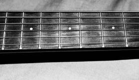 儿童` s声学吉他串和苦恼的黑白照片紧跟在吉他后面音乐课的 免版税库存照片