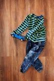 儿童` s夹克和牛仔裤有蓝色玩具汽车的在木背景 免版税库存图片