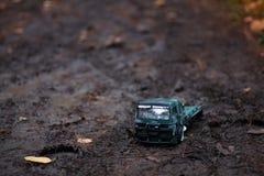儿童` s室外戏剧 运载一辆玩具卡车孩子的图象,装载用沙子 免版税库存照片