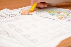 儿童` s手写并且显示在笔记本的英国与铅笔和毡尖的笔的信件和字母表 免版税库存照片