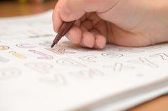 儿童` s手写并且显示在笔记本的英国与铅笔和毡尖的笔的信件和字母表 免版税库存图片