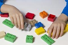 儿童` s手和五颜六色的玩具大厦立方体 顶视图 库存图片