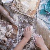 儿童` s手和面团用面粉在一张木桌上和一个绿色毛巾、滚针和委员会 库存图片