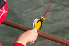 儿童` s手在一根小钓鱼竿钓鱼 Ozernaya渔 免版税库存图片