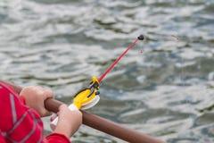 儿童` s手在一根小钓鱼竿钓鱼 Ozernaya渔 免版税库存照片