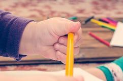 儿童` s手拿着一支黄色铅笔 免版税图库摄影