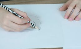 儿童` s手的特写镜头画与在白皮书的一支简单的铅笔 顶视图 库存照片