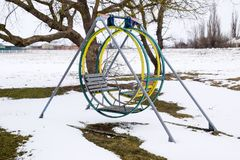 儿童` s操场在雪下的冬天 摇摆、转盘和幻灯片 冬天荒芜 免版税库存图片