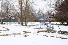儿童` s操场在雪下的冬天 摇摆、转盘和幻灯片 冬天荒芜 免版税库存照片