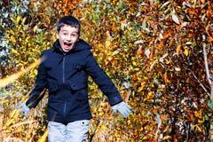 儿童` s时尚 秋天儿童` s衣物 一件黑夹克的一个男孩在黄色背景 不拘形式的样式 库存图片