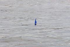 儿童` s有一个蓝色风帆的玩具小船在水 免版税图库摄影