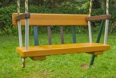 儿童` s木摇摆是黄色的在绳索 免版税库存图片