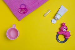 儿童` s牙膏和刷子在黄色背景、儿童` s玩具和乳头 免版税库存图片
