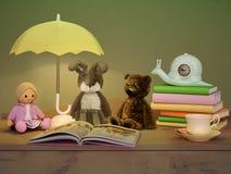 儿童` s玩具,书,时钟,灯位于桌 免版税库存图片