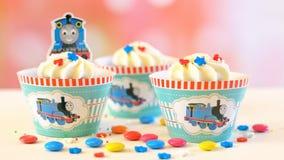 儿童` s生日聚会托马斯煤水柜机车主题的杯形蛋糕 库存图片
