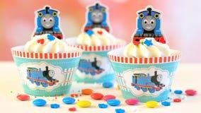儿童` s生日聚会托马斯煤水柜机车主题的杯形蛋糕 库存照片