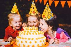 儿童` s生日聚会 在桌上吃蛋糕用他们的手和抹上他们的面孔的三个快乐的儿童女孩 乐趣a 免版税库存照片