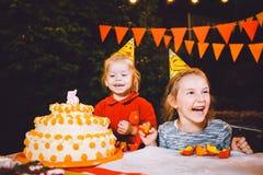 儿童` s生日聚会 在桌上吃蛋糕用他们的手和抹上他们的面孔的三个快乐的儿童女孩 乐趣a 免版税图库摄影