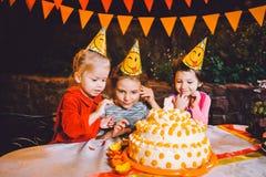 儿童` s生日聚会 在桌上吃蛋糕用他们的手和抹上他们的面孔的三个快乐的儿童女孩 乐趣a 图库摄影