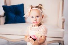 儿童` s生日 站立对房子卧室长沙发的背景桃红色礼服的滑稽的两岁的白种人女孩和吃 免版税库存照片