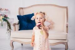 儿童` s生日 站立对房子卧室长沙发的背景桃红色礼服的滑稽的两岁的白种人女孩和吃 库存图片