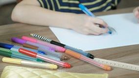 儿童` s的特写镜头递油漆与一支蓝色毛毡笔的图片在白皮书 侧视图 股票录像