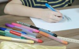 儿童` s的特写镜头递油漆与一支蓝色毛毡笔的图片在白皮书 侧视图 免版税库存照片