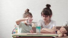 儿童` s科学 孩子混合化工试剂并且观察反应