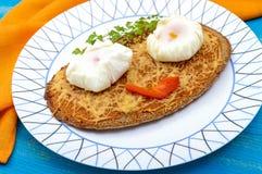 儿童` s菜单:黑黑麦面包热的三明治用搓碎干酪和一个荷包蛋在一块板材在蓝色木背景 库存图片