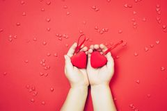 儿童` s递拿着在红色背景的红色心脏 顶视图,平的位置 St华伦泰` s comcept 图库摄影