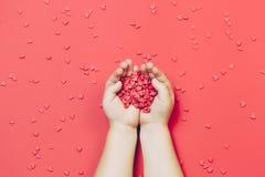 儿童` s递拿着在红色背景的红色心脏 顶视图,平的位置 St华伦泰` s comcept 库存图片