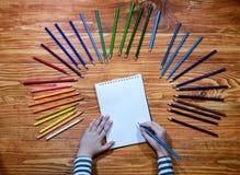 儿童` s递画在一个笔记本的一朵花有在木桌上的颜色铅笔的 库存照片