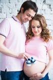 儿童` s鞋子在一个年轻爸爸的手上一名孕妇的腹部的背景的 库存照片