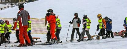 儿童` s高山滑雪学校 五颜六色的滑雪设备的辅导员和儿童学生 免版税库存图片